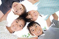 Four children 5-9 in huddle outdoors, portrait