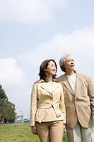 Mature couple in park, looking away