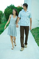 Young couple holding hands as they walk down sidewalk, looking out of frame