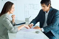Female real estate agent pointing to document, man signing, blueprints in foreground and background