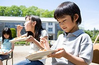 Children 7-9 eating curry in school playground