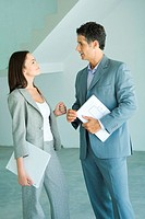 Well dressed man and woman standing in bare home interior, speaking, woman holding binder, man holding blueprints