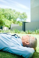 Mature businessman lying on ground outdoors, hands behind head, eyes closed, side view