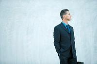 Businessman standing, looking away, hand in pocket