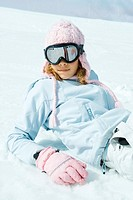 Preteen girl wearing ski gear, reclining in snow, portrait