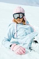 Preteen girl wearing ski gear, reclining in snow, portrait