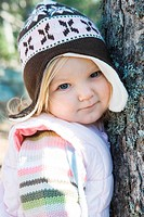 Toddler girl, leaning against tree trunk, looking at camera, portrait