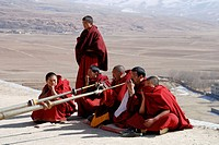 monks playing the long tibetan Ragdun - horn on the roof of the Garze monastery ,Sichuan,China