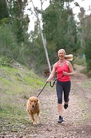 Active senior woman, in pink sports vest and leggings, running with golden retriever along woodland path, laughing, front view