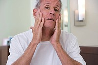 Senior man, in white t-shirt, applying moisturiser to face in bathroom, close-up, front view, portrait