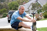 Active senior man, in blue t-shirt and shorts, warming up on driveway wall, stretching legs