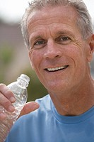 Active senior man, in blue t-shirt, drinking water from plastic bottle, smiling, close-up, portrait
