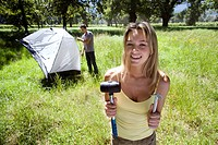 Young couple assembling dome tent on camping trip in woodland clearing, focus on woman holding tent peg and mallet in foreground, smiling, portrait