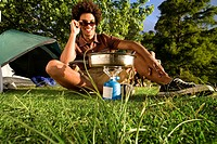 Young man, in sunglasses, cooking food on gas camping stove, smiling, front view, portrait surface level