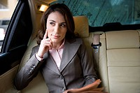 Businesswoman sitting in backseat of car, holding financial broadsheet newspaper, looking out of window, thinking, front view