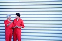 Two car mechanics, in red overalls, standing outside closed rolling garage door with clipboard and pen, talking