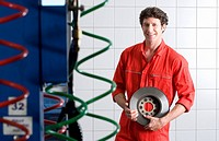 Male car mechanic, in red overalls, standing in commercial garage, holding vehicle part, smiling, portrait
