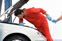Male care mechanic, in red overalls and protective gloves, looking at car engine in auto repair shop, colleague passing wrench, side view