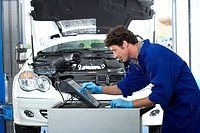 Male car mechanic, in blue overalls, using computer in auto repair shop, profile, car with open bonnet in background