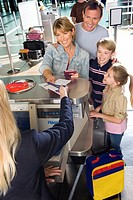 Family checking in at airport check-in counter, woman passing tickets to female airline check-in attendant, smiling