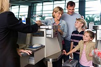 Family checking in at airport check-in counter, woman passing tickets to female airline check-in... (thumbnail)