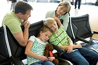 Parents looking at children sleeping on seats in airport departure lounge, girl 7-9 holding soft toy