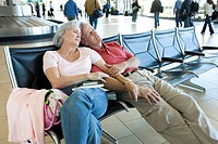 Senior couple sitting in airport departure lounge, leaning against each other, arm in arm, sleeping