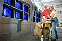 Senior couple standing with luggage trolley beside row of flight information screens in airport, arms around each other, smiling, portrait