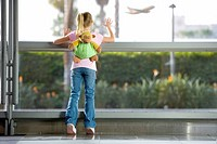 Girl 7-9, with ÔÇÿmonkeyÔÇÖ rucksack, looking through large window in airport departure lounge, leaning against glass, watching aeroplane taking off, ...