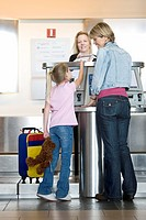 Mother and daughter 7-9 checking in at airport check-in desk, female check-in attendant passing boarding passes to girl, smiling, rear view