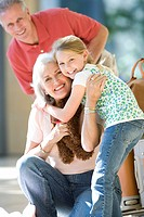 Grandmother and granddaughter 7-9 embracing in airport, senior woman crouching, holding soft toy, father in background, smiling, portrait