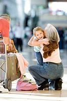 Grandmother and granddaughter 7-9 embracing beside luggage trolley in airport, grandfather looking on, senior woman crouching, girl holding soft toy, ...