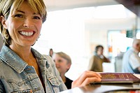 Woman standing at airport check-in desk with passport, son 8-10 in background, focus on woman, smiling, close-up, side view, portrait