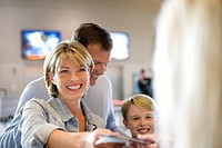Family standing at airport check-in desk, woman handing passports to check-in attendant, smiling differential focus