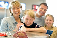 Family checking in at airport, boy 8-10 handing over passports, smiling, view from behind check-in desk, focus on foreground