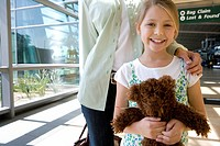 Mother and daughter 7-9 standing in airport, focus on girl holding teddy bear, smiling, front view, portrait