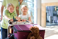 Family pushing luggage trolley in airport, children 7-10 smiling, focus on teddy bear and suitcases in foreground