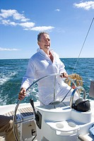 Mature man standing at helm of yacht out at sea, steering, smiling