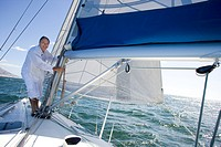 Mature man standing on deck of yacht out at sea, making adjustments to rigging, smiling, side view, portrait tilt