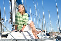Mature woman, in green striped jumper, sitting on deck of yacht moored at harbour jetty, legs crossed at knee, looking away, thinking