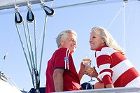 Mature couple, in red jumper and t-shirt, sitting on deck of yacht moored at harbour jetty, holding wine glasses filled with champagne, smiling, low a...