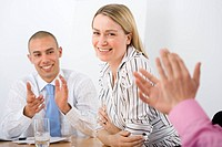 Business colleagues applauding businesswoman during meeting, smiling, portrait differential focus