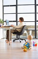 Man using computer by window in home office, baby girl 21-24 months on floor with toys, side view