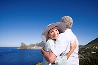 South Africa, Cape Town, senior couple embracing by sea, smiling, portrait of woman
