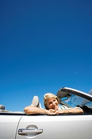 Senior woman sitting in passenger seat of convertible silver car, smiling, portrait, low angle view