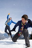 Two young men having snow fight in snow field