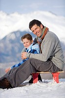 Father and son 7-9 sitting on sled in snow field, smiling, portrait, mountain range in background