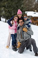 Family of four embracing in snow field, wearing sunglasses, smiling, portrait