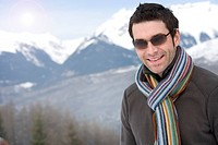 Young man wearing woolen scarf and sunglasses outdoors, portrait, close-up, mountain range in background