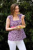 Young pregnant woman eating salad outdoors, smiling, portrait